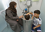 Three-year old Anas, who suffered a severe burn to her chest, is comforted by her mother Ola Yasin and her 8-year old brother Zeki as the girl sits in a therapeutic bath in the Al Ahli Arab Hospital in Gaza City. The Anglican Church-affiliated hospital is a member of the ACT Alliance.<br /> <br /> The 2014 war provoked serious damage to Gaza's health infrastructure. Seventeen hospitals, 56 primary health care facilities and 45 ambulances were damaged or destroyed. Sixteen health care workers were killed and 83, most of them ambulance drivers and volunteers, were injured.