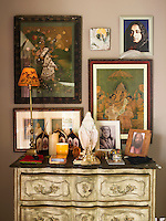 A collection of Indian prints and photographs hang above a French chest of drawers in the bedroom