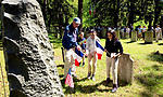 WATERBURY, CT-052118JS09--William Pierpont, left, directs Generali school fifth grade students, from left, Marissa Taylor, Sofia Martinez and Juleimy Serrano, where to place the French flags and wreath during a Memorial Day ceremony Monday at East Farms Cemetery.  The event commemorates the lives of 24 soldiers, including 2 unknown French soldiers who marched with General Rochambeau on his journey to meet General Washington in 1781. American flags, along with two French flags, as well a wreath, were placed on the graves and memorials inside the cemetery. <br /> Jim Shannon Republican American