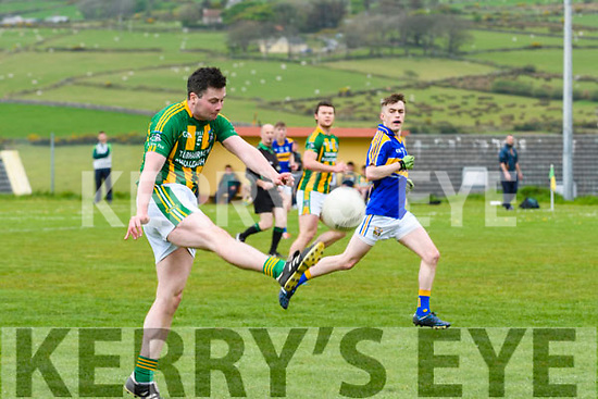 Lios Póil Daran Ó Cearbhúil in an action watched by Cordal Gary O'Leary during the Junior Football Championship match at Lispole GAA Grounds on Sunday afternoon.