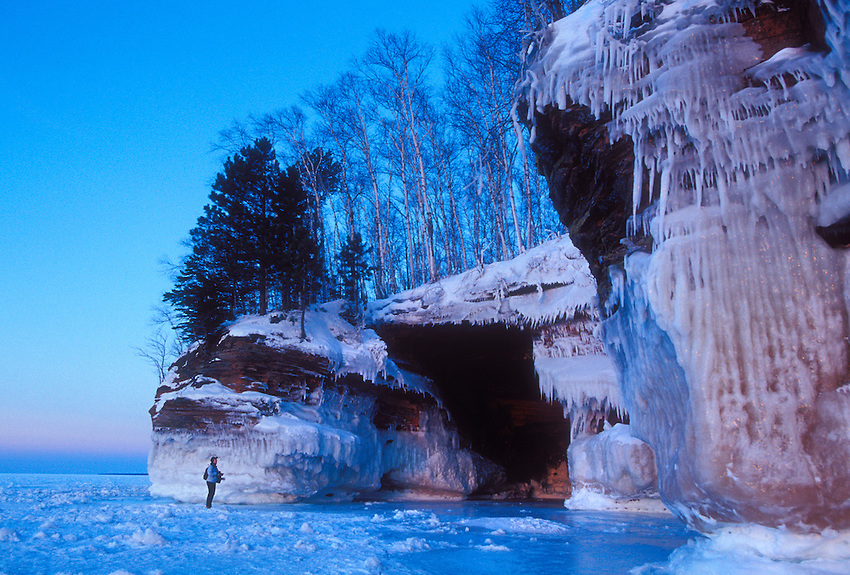 A photographer stops to ponder the ice-covered sea caves of Lake Superior at Squaw Point in Apostle Islands National Lakeshore near Bayfield, Wis.