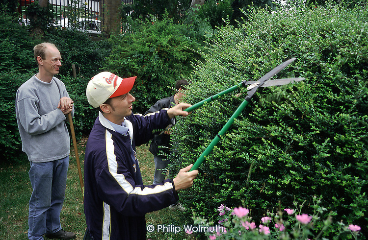 A trainee and supervisor trim a hedge at the Hoxton Trust Gardening Project in the Hoxton Community Garden, Hackney, East London.