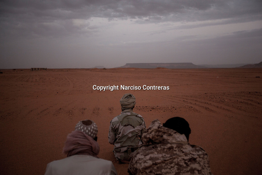 Toubou militiamen pray at dusk in the middle of the desert, far down towards the border with Niger in the south of Libya.