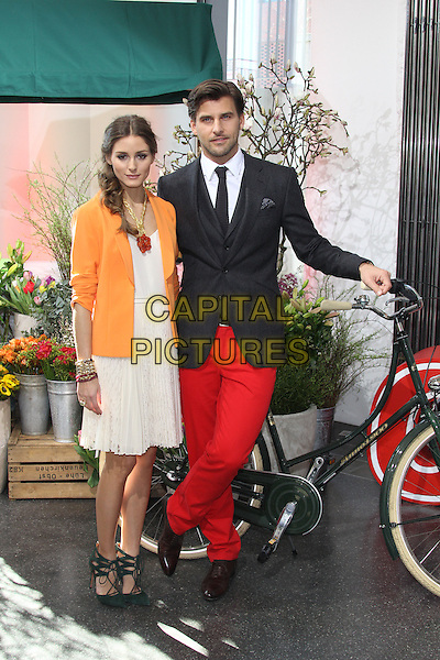 "Olivia Palermo & Johannes Huebl.Photocall for the new faces of ""OTTO""-group (online seller) presenting duos Oliva Palermo and partner Johannes Huebl, location ""Prototype"", Hamburg, Germany..March 5th, 2013.full length jacket red necklace gold dress red jeans trousers couple orange blazer braid plait hair loose white shirt blue bike bicycle knitted tie grey gray suit stubble facial hair .CAP/UNT.©Unit2/Capital Pictures"