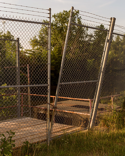 August 5, 2016. Flint, Michigan.<br />  A broken fence guards the entrance to the intake pipe that brought water from the Flint River into the Water Plant. Now that the city has reverted back to getting water from Detroit, mucho the Plant is off line. <br />  In April 2014, the city of Flint switched its water source from the Detroit Water and Sewerage Department to using the Flint River in an effort to save money. When the switch occurred, the city failed to have corrosion control treatment in place for the new water. This brought about a leaching of lead from pipes into the water, increasing the lead content in the drinking water to levels far above legal limits. After independent sources brought this to light, the city admitted the water was unsafe and legal battles have ensued between resident and the local and state governments.