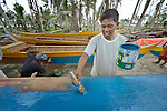 A man paints a new fishing boat on Jinamoc Island, part of the municipality of Basey in the Philippines province of Samar that was hit hard by Typhoon Haiyan in November 2013. The storm was known locally as Yolanda, and left most of the island's boats, nets, and houses destroyed. The ACT Alliance has been providing a variety of assistance to survivors here, and is planning a long-term rehabilitation program with residents.