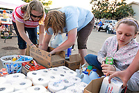 Sara Goldberg (center), along with daughters Sabrina Guilmette (left, 13 years old) and Jasmine Guilmette (right, 11 years old) sift through donated cleaning supplies to hand out in the Nashville suburb of Bellevue on Saturday, May 8, 2010.