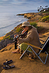 Young woman playing guitar at Sunset Cliffs, San Diego, California