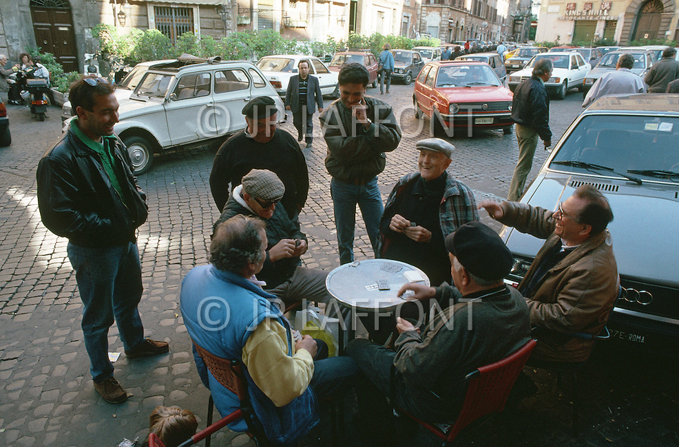"April 27, 1990, Rome, Italy. Photographing for the book ""One day in the life of Italy"", this is an exploration of Rome. At the end of the day, in Piazza San Callisto, men gather to play cards."