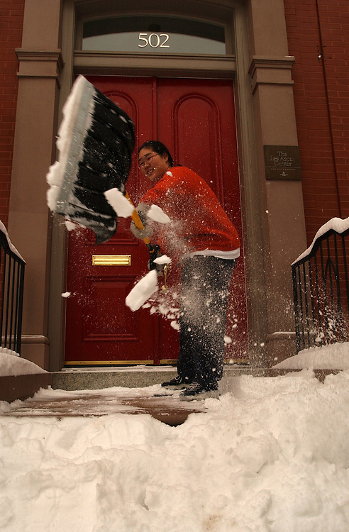 Min Roh, an intern for the FDA, shovels the steps outside the Les Aspin building where she is sponsered as intern, Monday.