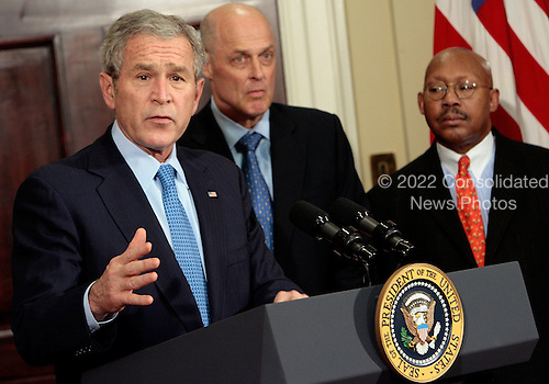 WASHINGTON - DECEMBER 20:  (AFP OUT) U.S. President George W. Bush is joined by Treasury Secretary Henry Paulson and Housing and Urban Development Secretary Alphonso Jackson before signing the Mortgage Forgiveness Debt Relief Act of 2007 in the Roosevelt Room at the White House December 20, 2007 in Washington, DC. The act is an attempt by Congress and the Bush administration to stave off the effects of the sub-prime mortgage crisis which continues threaten the U.S. economy.  (Photo by Chip Somodevilla/Getty Images)