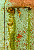 Detail of blue door handle with fall leaf hanging, rust and chipped paint