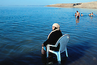 Jordan. Dead sea. Jordanians tourists (muslim boys) takes a bath, swimm and float on the salt water. An old woman, seated on a plastic chair and her feet in the water, enjoyes herself on a sunny friday afternoon. The woman wear a long dress and a veil on her head as part of muslim tradition and religion. Friday is the day off (resting day) in the arabian culture. On the other side of the sea is Palestine and the West Bank (Occupied Territories by Israel).  © 2002 Didier Ruef