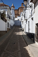 View up a cobbled street towards the church in the village of Aracena in Andalucia southern Spain