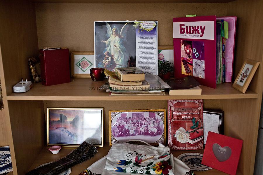 UKRAINE, Mariupol: Some christian decoration and books around a shelf. <br /> <br /> <br /> UKRAINE, Mariupol: Certains d&eacute;coration chr&eacute;tienne et livres autour d'une armoire.