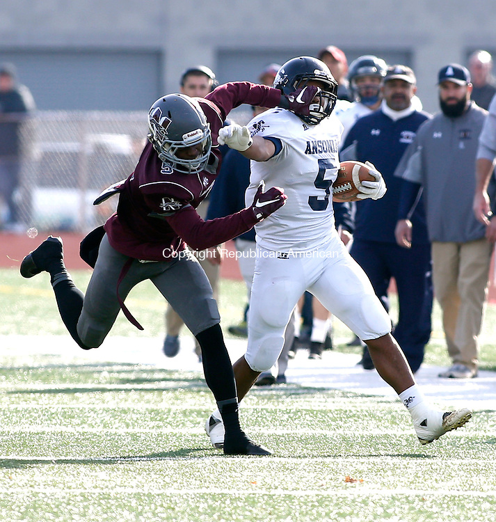 Naugatuck, CT- 26 November 2015-112615CM10-  Ansonia's Tyler Bailey (5) stiff arms Naugatuck's Dan Oladapo as he tries to bring him down during their Thanksgiving matchup in Naugatuck on Thursday.  The Chargers would rout the Greyhounds,  41-8.   Christopher Massa Republican-American