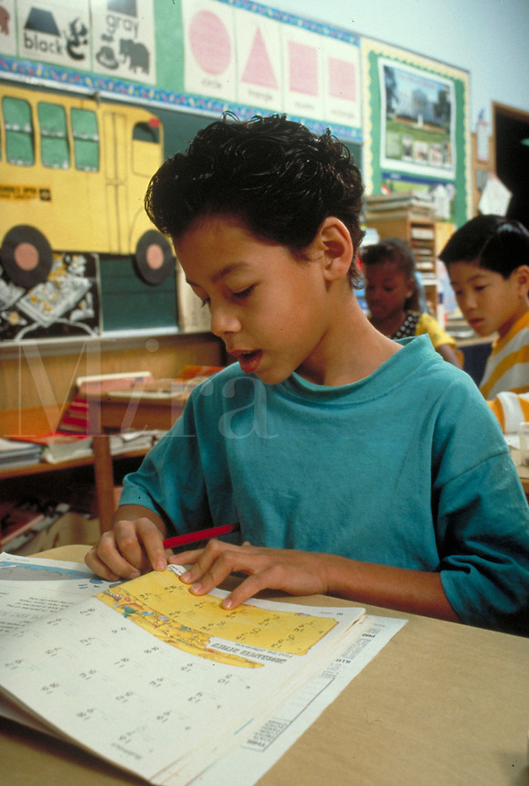 HISPANIC BOY (8) WORKING ON MATH PROBLEM AT HIS DESK IN CLASS. HISPANIC BOY (8). OAKLAND CALIFORNIA.