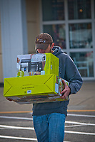 Shopping on Christmas Eve, a man uses his chin to steady two housewares items he bought at a local Kohl's store. The man, who did not provide his name, didn't wait for gift wrapping at the store for the coffee maker and electric skillet. The line was too long.