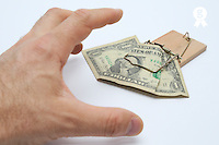Man's hand about to catch dollar banknote on mousetrap (Licence this image exclusively with Getty: http://www.gettyimages.com/detail/sb10068346an-001 )