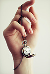 Young female hand holding necklace with open watch