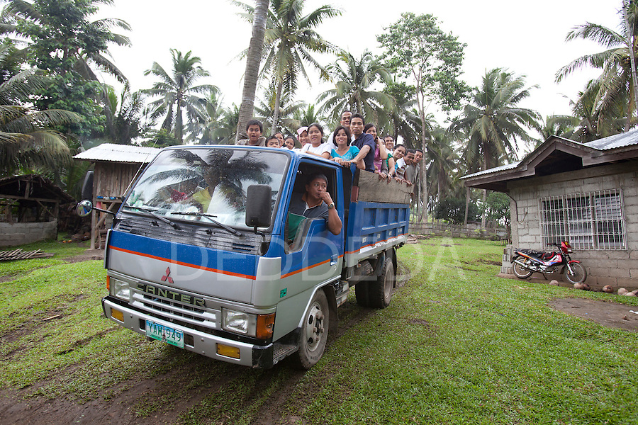 Wedding guests pile in the back of a large dump truck that they used for transportation to and from a wedding reception in a rural area near San Jose on Negros Island, Philippines.