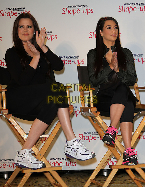 KHLOE KARDASHIAN & KIM KARDASHIAN.Khloe Kardashian, Kourtney Kardashian.Skechers Shape-Ups Announces Global Partnership With Kim Kardashian And Kris Jenner held at The Beverly Hills Regent Hotel, Beverly Hills, CA, USA..November 22nd, 2010.full length black leggings jacket trainers sneakers sitting chair hands clapping .CAP/ADM/KB.©Kevan Brooks/AdMedia/Capital Pictures.