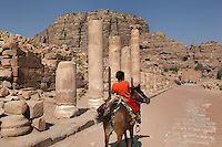 Boy riding donkey down Colonnaded Street, c. 106 AD, Petra, Ma'an, Jordan. The street was originally lined with a double row of columns, built by the Romans over an earlier Nabatean road. Markets were probably held here 100-200 AD. Ruins of the city centre scatter this area. Petra was the capital and royal city of the Nabateans, Arabic desert nomads. Picture by Manuel Cohen