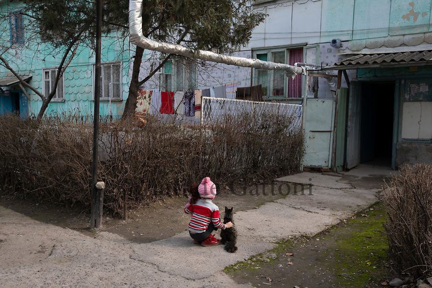 Uzbekistan - Tashkent - A little girl sits next to her cat in the neighborhood of Sputnik, built in 1966 after the earthquake to relocate part of the 300,000 people who had lost their house. The wooden houses were meant to cover the emergency but the area is still inhabited.