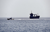 Pictured: A Coastguard vessel (L) patrols the area near the oil spill that has reached the coast of Salamina, Greece<br /> Re: An oil spill off Salamina island&rsquo;s eastern coast is spreading and has become &ldquo;an environmental disaster&rdquo; according to local authorities in Greece.<br /> The spill was caused by the sinking of the Aghia Zoni II tanker, carrying 2,200 metric tons of fuel oil and 370 metric tons of marine gas oil on Saturday, southwest of the islet of Atalanti near Psytalleia. According to reports, the coastline stretching from Kinosoura to the Selinia community has &ldquo;turned black&rdquo; and authorities fear a new leak from the sunken ship.<br /> According to the island&rsquo;s mayor, Isidora Papathanasiou, the weather &ldquo;turned on Sunday afternoon and brought the oil spill to Salamina.&rdquo;
