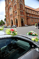 Car decorated with flowers as part of a wedding party, outside the Gothic Revival styled Saigon Notre-Dame Cathedral Basilica. The cathedral was built between 1863 and 1880, the statue was installed in 1959. Ho Chi Minh City (Saigon), Vietnam