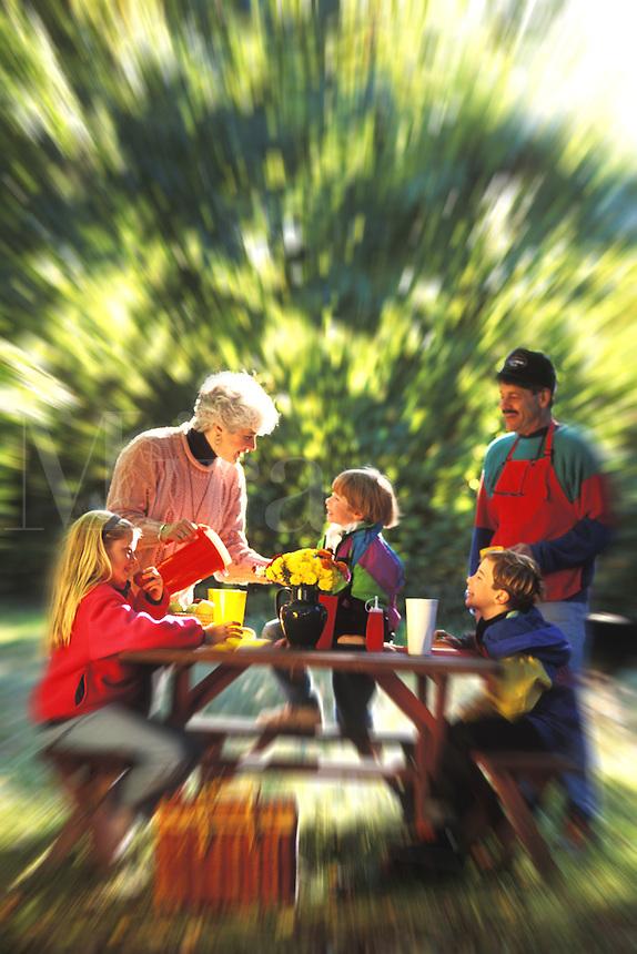 Family outdoors having a picnic.
