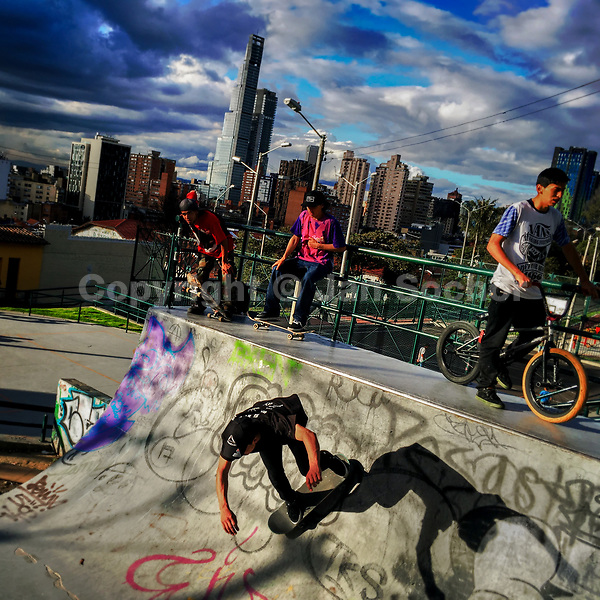 A Colombian skateboarder rides on a skateboard ramp, while being watched by his fellows, in the park of La Concordia, Bogotá, Colombia, 25 November 2017.