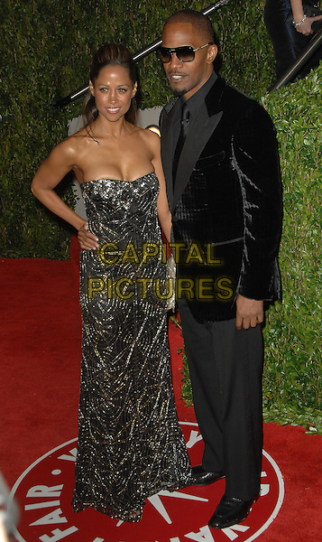 STACEY DASH & JAIME FOXX.The 2010 Vanity Fair Oscar Party held at The Sunset Tower Hotel in West Hollywood, California, USA..March 7th, 2010.oscars full length black suit strapless beds beaded maxi dress hand on hip gold silver jamie couple sunglasses shades.CAP/RKE/DVS.©DVS/RockinExposures/Capital Pictures.