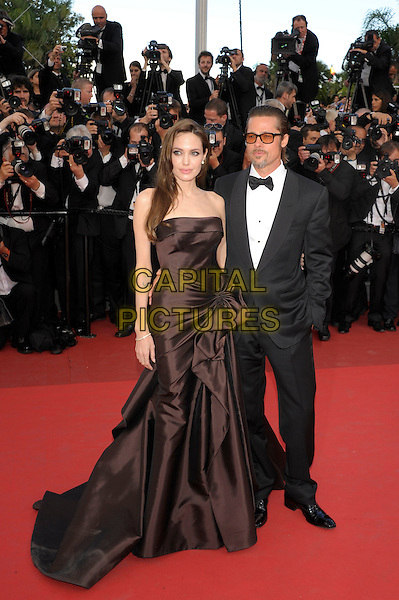 ANGELINA JOLIE & BRAD PITT.'The Tree of Life' premiere at the Palais des Festival, 64th International Cannes Film Festival, France.16th May 2011.full length strapless silk satin brown dress gown black tux tuxedo tinted glasses sunglasses shades couple gathered goatee facial hair photographers press.CAP/PL.©Phil Loftus/Capital Pictures.