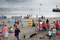 View of Looe beach with children's activities happening on an overcast day with the sea in the background. Looe, Cornwall, UK