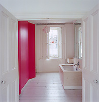 Double doors lead into the minimal white bathroom with one wall of bright pink floor-to-ceiling cupboards