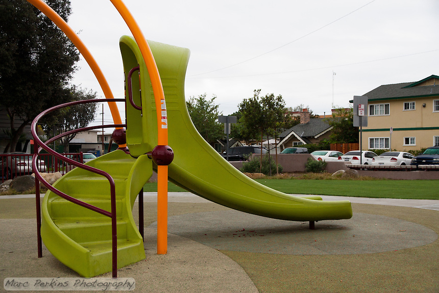 The slide of the play structure at Circle Park, a pocket park located on Park Circle Drive in Anaheim, California.  Seen on a cloudy, rainy day with the artificial turf lawn visible in the background.