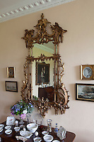 An elaborate 18th century gilt-framed mirror hangs above a display of ceramics in the drawing room
