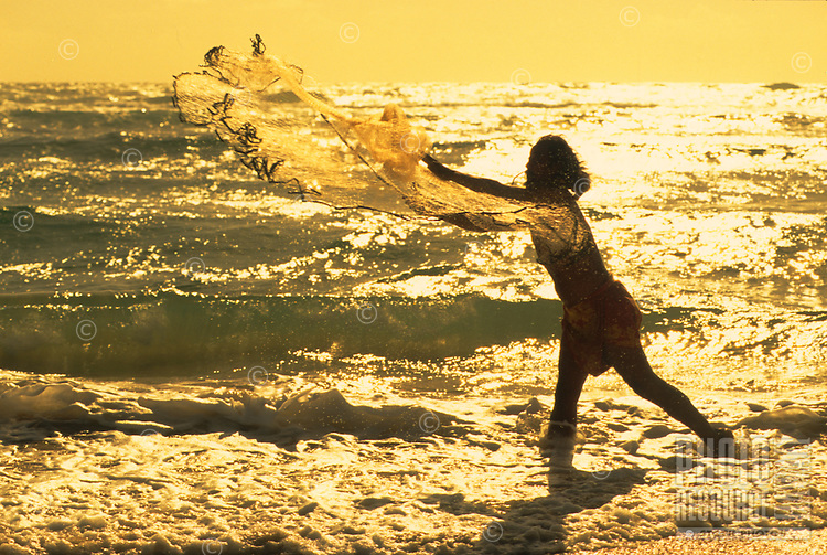 Hawaiian man casting his throw net on the ocean's edge at sunset.