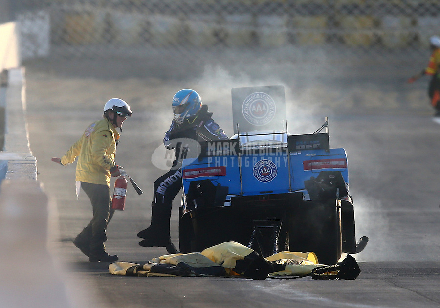 Feb 12, 2016; Pomona, CA, USA; NHRA funny car driver John Force climbs from his car after an explosion and small fire during qualifying for the Winternationals at Auto Club Raceway at Pomona. Mandatory Credit: Mark J. Rebilas-USA TODAY Sports