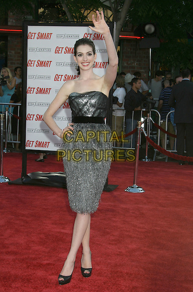 "ANNE HATHAWAY.""Get Smart"" Los Angeles Premiere held at Mann's Village Theatre, Westwood, California, USA..June 16th, 2008.full length black sash waist belt hands on hips grey gray silver strapless dress platform peep toe shoes heels hand arm in air waving .CAP/ADM/MJ.©Michael Jade/AdMedia/Capital Pictures."