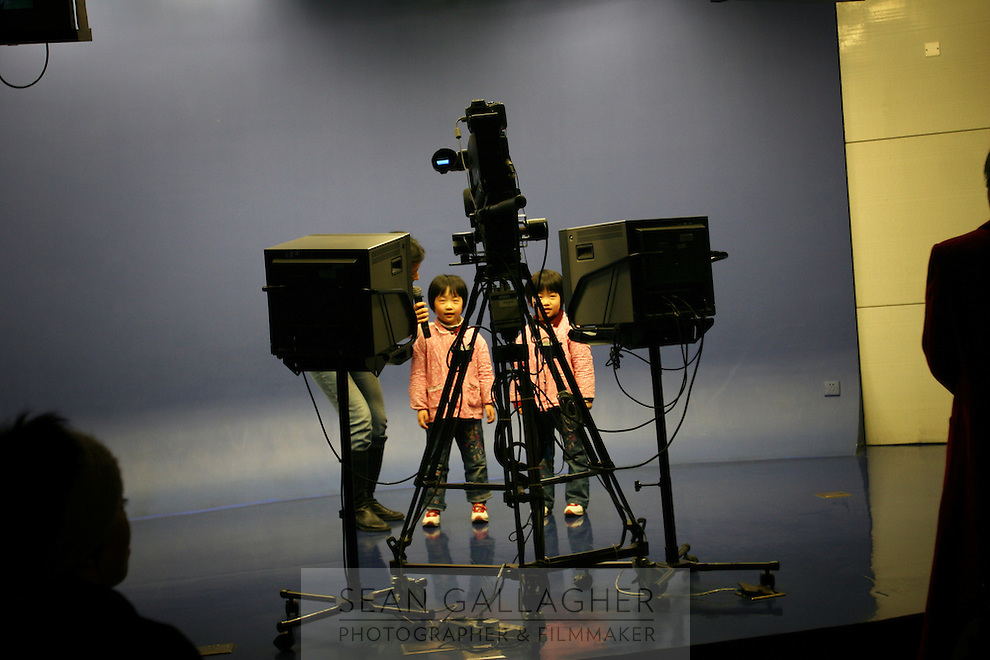 CHINA. Shanghai.  Two children in a mock television studio in the Shanghai Science and Technology Museum (?????; pinyin: Shàngh?i ke¯jì gu?n) is a large museum in Pudong, Shanghai, close to Century Park, the largest park of the city. The construction of the museum cost 1,75 billion RMB, and the floor area is 98 000m2 .2008..