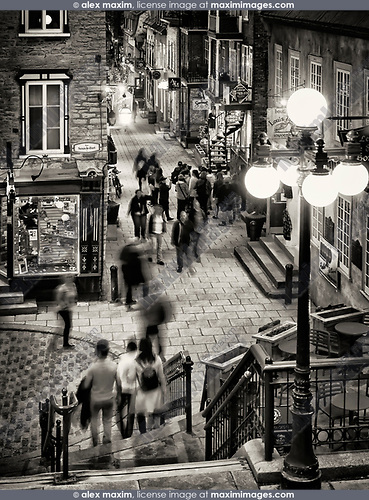 People walking at night on historic streets Rue du Petit Champlain and Rue Sous Le Fort of old Quebec City, view from above. Quebec, Canada. Black and white photo. Ville de Québec.