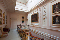 A pale pink and white landing approached by a staircase of gilded, wrough-iron banisters