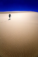 A hiker makes their way up Eureka Dunes at Death Valley National Park,California