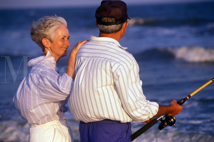 Senior couple surf fishing  at the beach