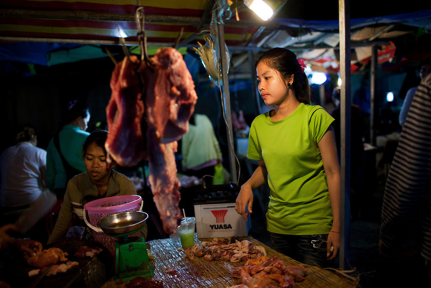 A worker from the Shen Zhou garment factory buys pork at an open-air market near the Vattanac Industrial Park following the overtime shift which ends at 6 p.m., Phnom Penh, Cambodia, Sept 12, 2011. Pork costs about US$5 per kilo, though a single worker may only spend between 60 to 75 cents (US) per day on meat.