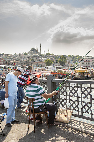 Man fishing on Galata Bridge, Suleymaniye Mosque in background, Istanbul, Turkey  May 2015.<br /> CAP/MEL<br /> &copy;MEL/Capital Pictures /MediaPunch ***NORTH AND SOUTH AMERICA ONLY***