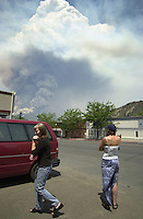 Residents in downtown Durango watch a plume of smoke rise from the Missionary Ridge Fire north of town, Colorado in June 2002.