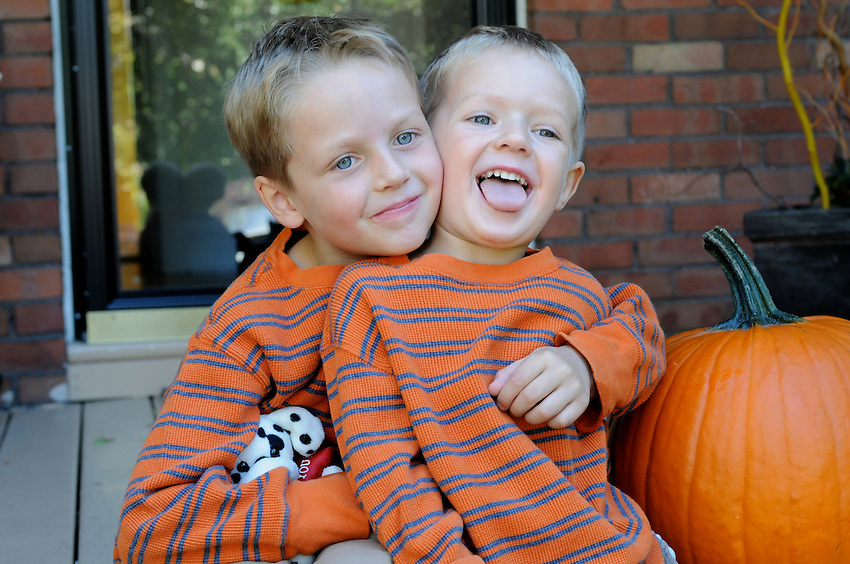 Brothers arm in arm, sitting on the porch, autumn colors, Halloween pumpkin